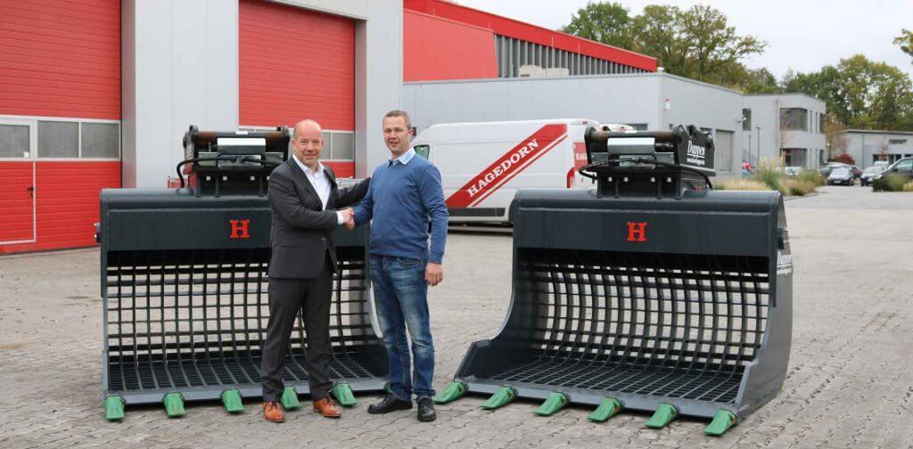 Dappen Werkzeug- und Maschinenbau | Unternehmensgruppe Hagedorn erweitert ihre Anbaugeräte um drei weitere Dappen-Sieblöffel | Handschlag von zwei Männern vor zwei großen Dappen Sieblöffeln